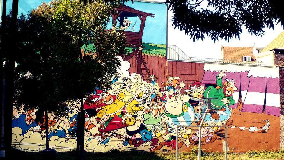 Fresque très colorée d'Astérix et ses amis sur le mur d'une aire de jeux – source; CC BY